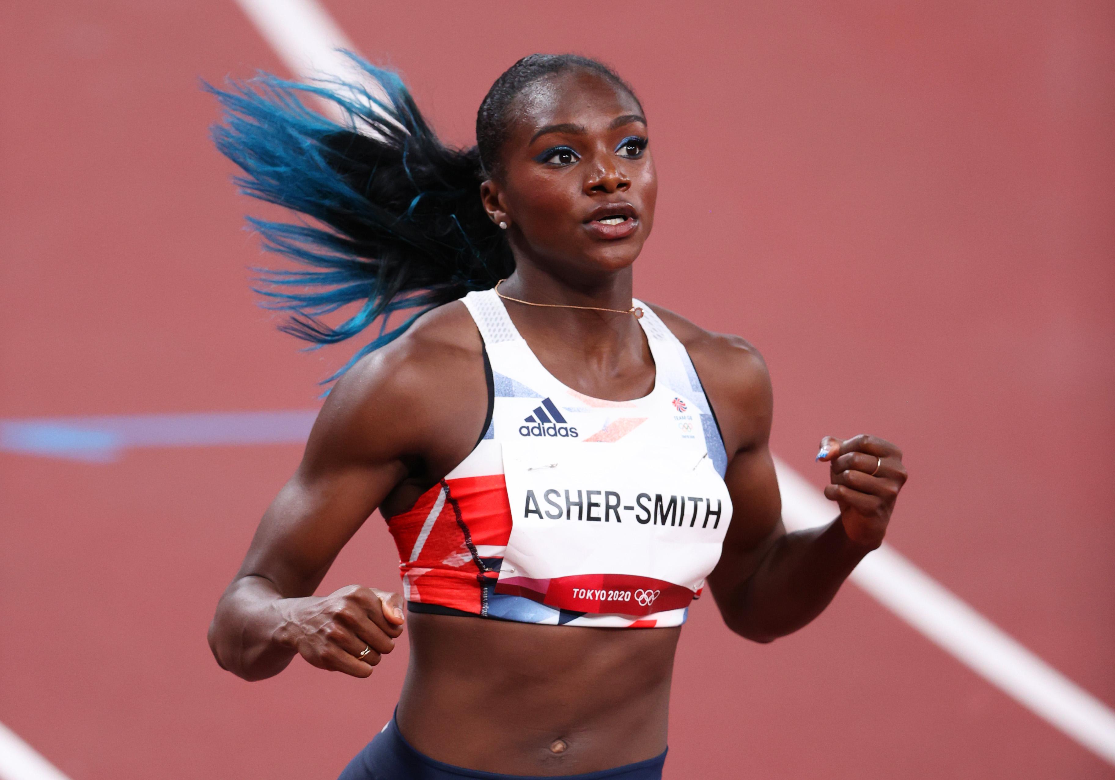 A velocista Dina Asher-Smith, da Grã Bretanha, nas Olimpíadas de Tóquio. Ela está com um top branco, cabelo amarrado em um rabo, enquanto corre na pista de atletismo.