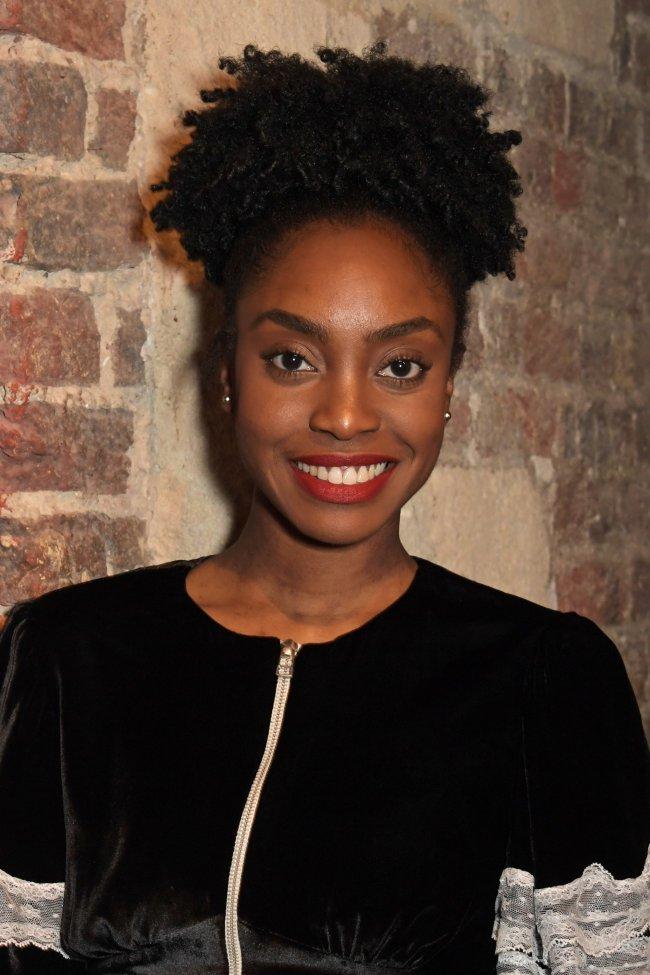 Anita-Joy Uwajeh posando para foto em uma parede de tijolos usando uma roupa preta com detalhes brancos e sorrindo para câmera