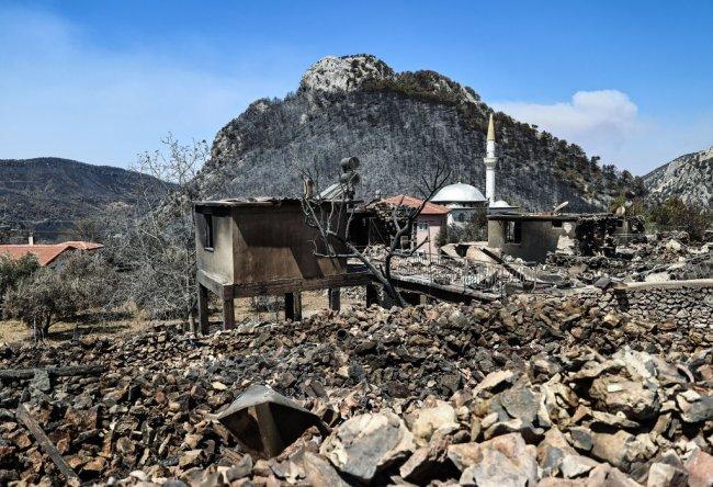 Escombros pós-queimada em uma região do sul da Turquia. Vemos restos de casas, muita pedra e uma montanha ao fundo totalmente desmatada