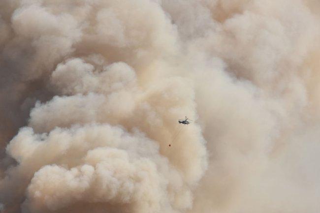 Foto de uma imensa nuvem marrom e de um helicóptero pequenininho sobrevoando na frente dela