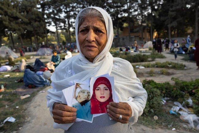 Uma senhora de 60 anos, vestindo um hijab branco e chorando, segura fotos de sua filha, que ela diz ter sido morta há um mês por membros do Talibã