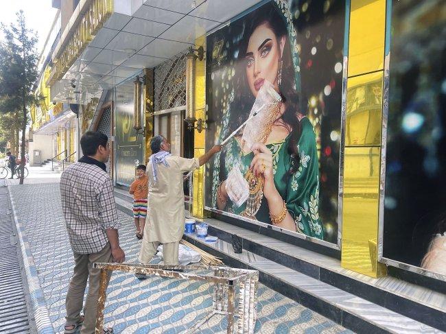 Homens escondem com tinta fotos de mulheres que estampavam a faixada do salão de beleza, após o Talibã ocupar Cabul