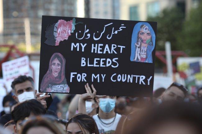 Foto de uma manifestação contra o Talibã lota de gente. Uma garota segura um cartaz com os dizeres: