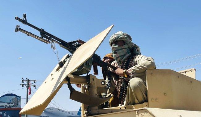 Foto de membros da Talibã, vestindo roupas militares, em cima de um tanque de guerra, apontando armas para o povo