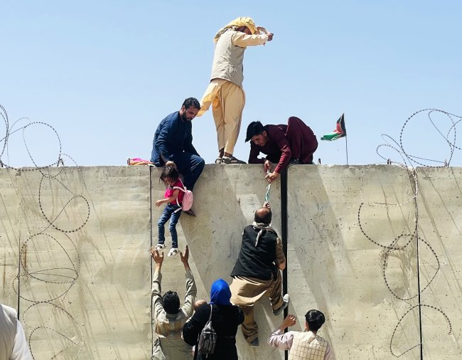 Afegãos escalam o muro do Aeroporto Internacional Hamid Karzai International, tentando pegar algum voo para fugir da capital Cabul, ocupada pelo Talibã