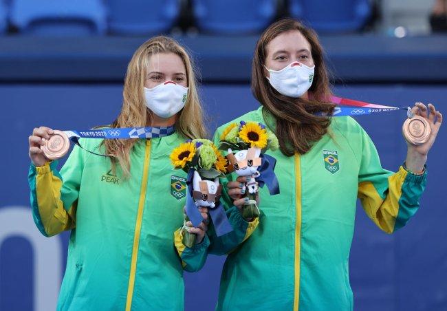 Laura Pigossi e Luisa Stefani no pódio, após conquistarem uma medalha olímpica inédita para o Brasil no tênis, em Tóquio