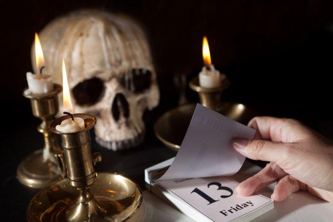 Na foto, um calendário marcando a sexta-feira 13, algumas velas ao redor dele e um crânio ao fundo