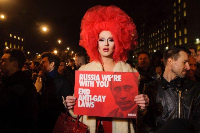 Drag protesta contra as leis anti_gays russa, segurando uma plava vermelha com a foto de Putin. Ela usa uma peruca vermelha e um casaco bege