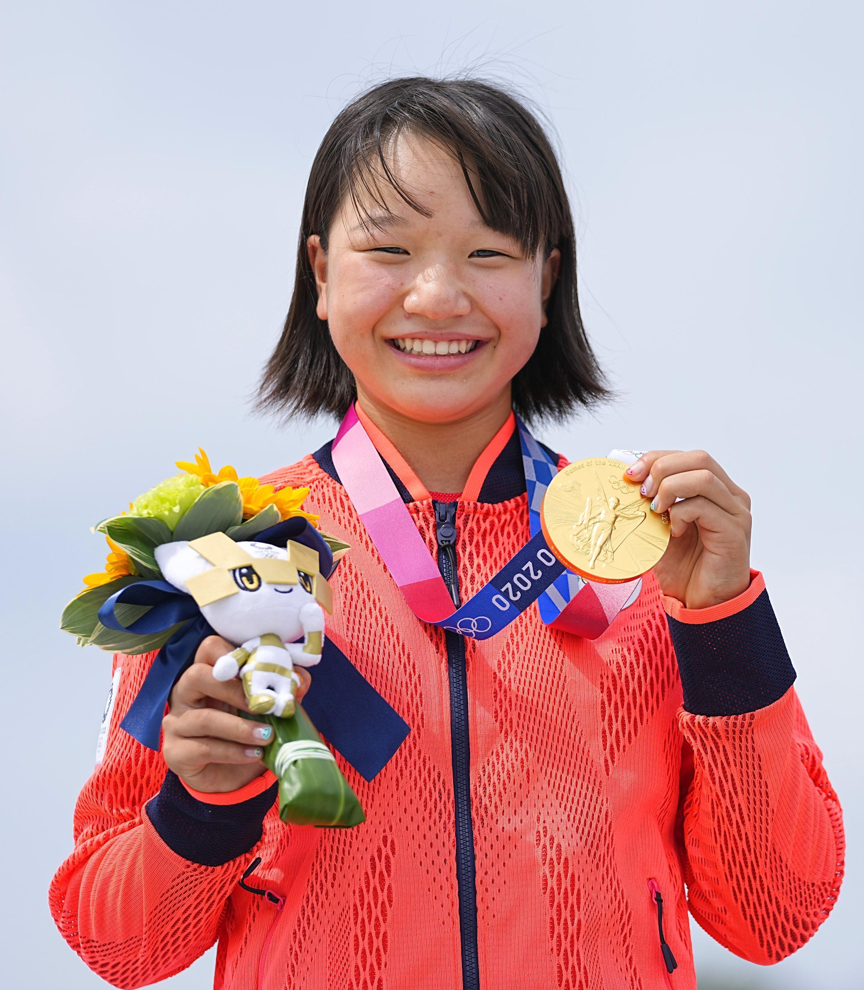 A skatista japonesa Momiji Nishiya, de 13 anos, sorrindo enquanto segura sua medalha de ouro e o mascote das Olimpíadas de Tóquio 2020.