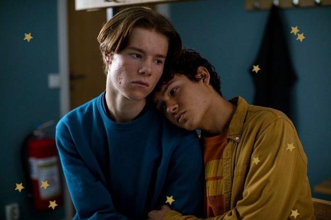Casal do seriado Young Royals juntos, Simon está com a cabeça apoiada no ombro de Wilhelm.
