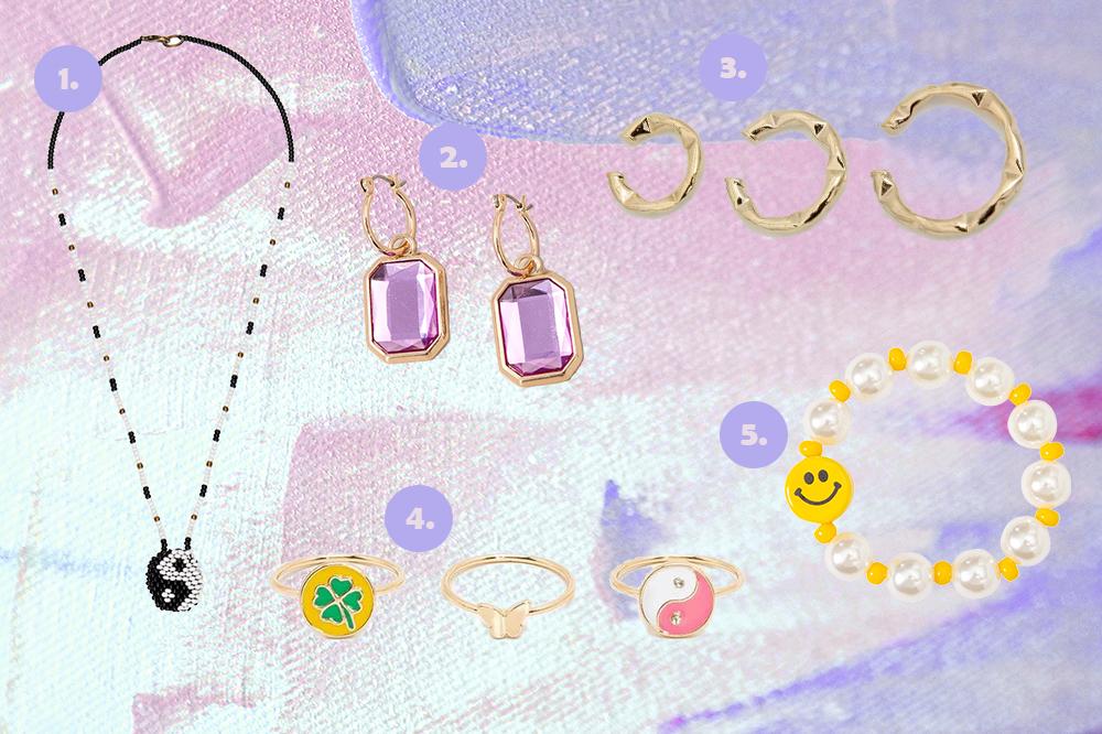 Montagem em fundo lilás e rosa com cinco opções de acessórios. Colar com símbolo yin yang feito à mão, brinco lilás, ear hooks dourados, kit de três anéis e pulseira de pérolas com carinha feliz.