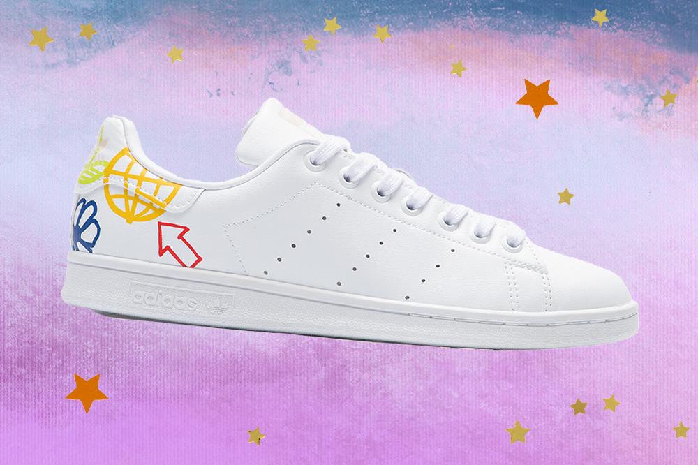 Montagem do tênis Adidas Stan Smith branco em fundo degradê de lilás e azul com estrelas douradas e laranjas