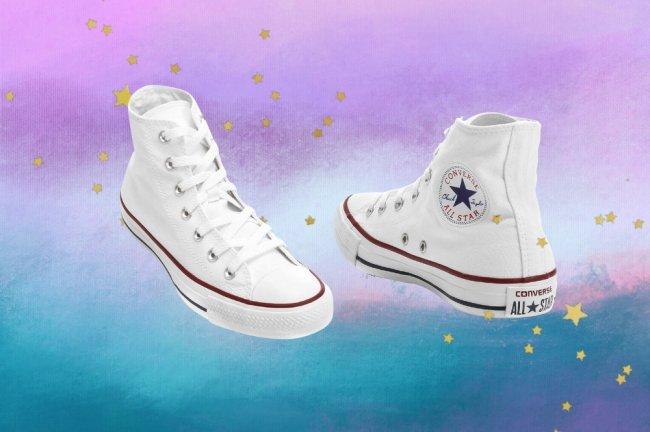 Montagem com o fundo degradê roxo e azul com detalhes de estrelas douradas com a foto do tênis branco de cano alto All Star da Converse.