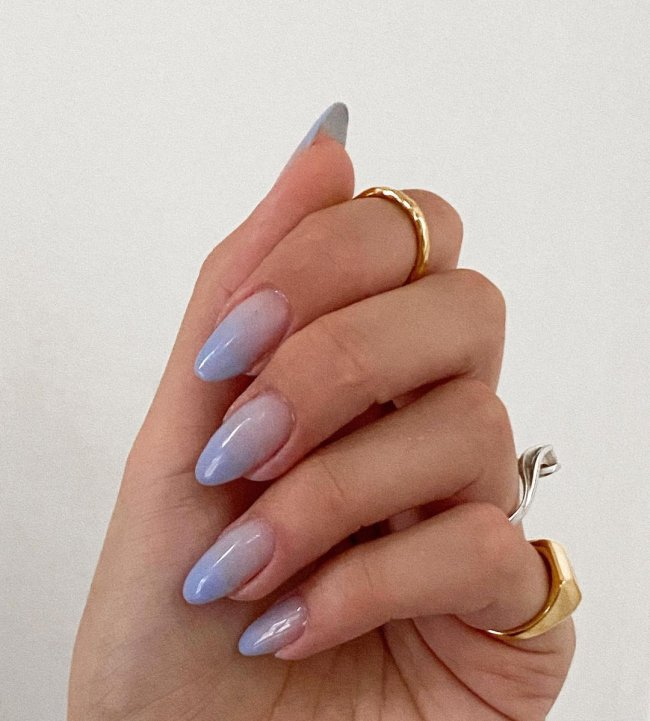 Foto de uma mão mostrando as unhas decoradas no estilo baby boomer na cor azul.