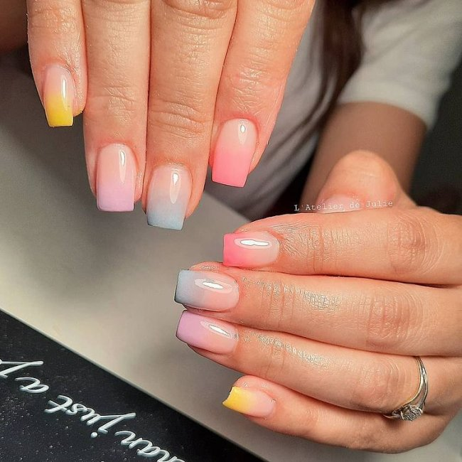 Foto de duas mãos com foco nas unhas decoradas no estilo baby boomer multicoloridas.