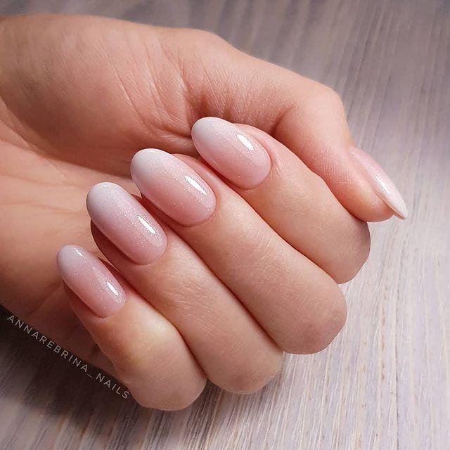Foto de uma mão com as unhas pintadas de branco no estilo baby boomer.