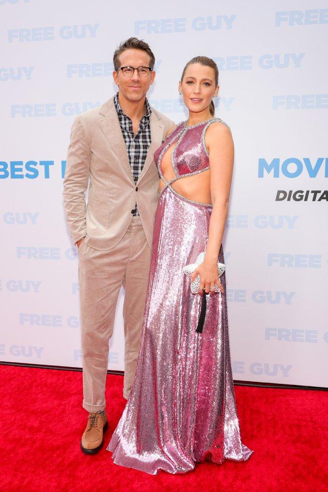 Foto dos atores Ryan Reynolds e Blake Lively na pré-estreia do filme Free Guy. Ela usa um vestido rosa e cabelo preso em um rabo de cavalo e ele usa um terno bege e óculos de grau. Ambos olham para a foto e apenas o Ryan sorri levemente.