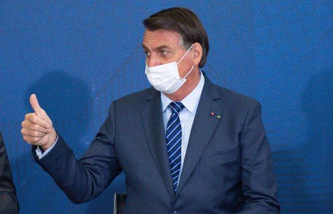 Jair Bolsonaro fazendo sinal de joinha com as mãos
