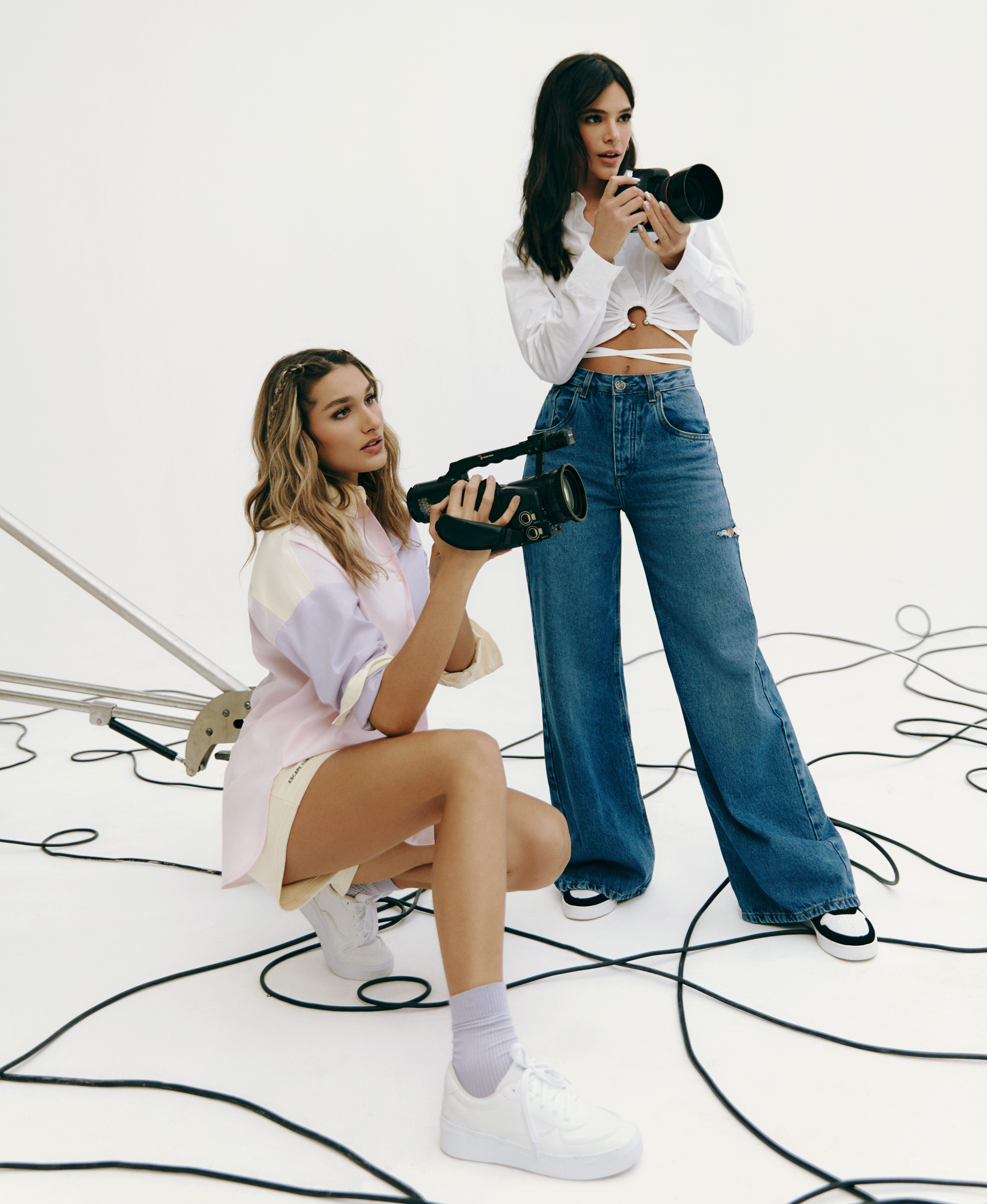 Sasha Meneghel e Bruna Marquezine. Sasha está agachada no chão com uma camisa e um tênis branco enquanto segura uma câmera. Bruna está em pé, com um cropped branco e calça jeans enquanto segura uma câmera.