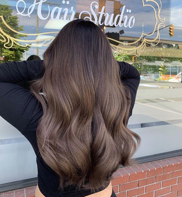 Foto de uma mulher de costas mostrando o cabelo. Ela usa uma blusa de manga longa preta e mostra o cabelo longo castanho acinzentado.