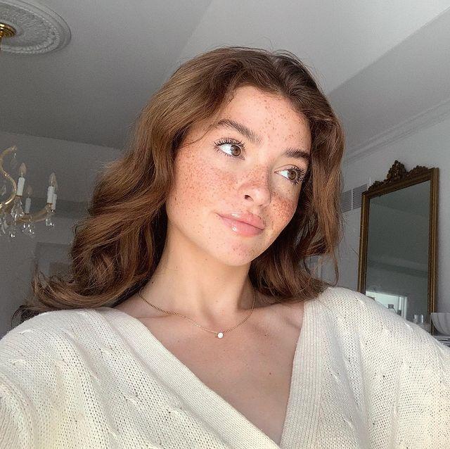 Selfie de uma mulher. Ela usa um cardigan branco, colarzinho dourado, cabelo castanho acobreado solto e maquiagem natural com gloss. Ela olha para o lado e sorri levemente.