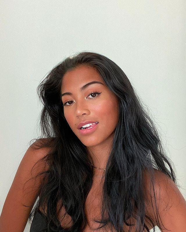 Selfie de uma mulher. Ela usa um top cropped preto, colarzinho dourado, está com o cabelo solto e maquiagem natural. Ela olha para a câmera e sorri levemente.