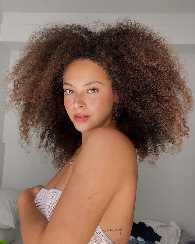 Foto de uma mulher. Ela usa um top branco, cabelo crespo castanho iluminado solto e maquiagem natural. Ela olha para a câmera e não sorri.