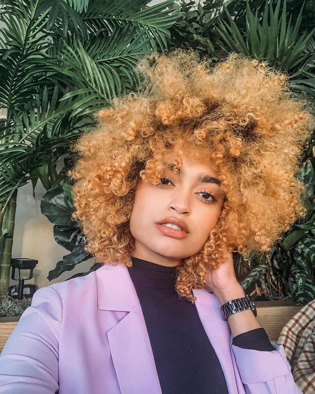 Selfie de uma mulher. Ela usa uma camiseta preta de gola alta, casaco lilás como sobreposição, relógio no braço esquerdo e cabelo cacheado ruivo claro solto. Ela olha para a câmera e não sorri.