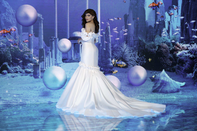 Caroline Priante usando vestido de noiva inspirado na Ariel. Ela está de costas com a cabeça levemente virada para o lado e expressão facial séria.