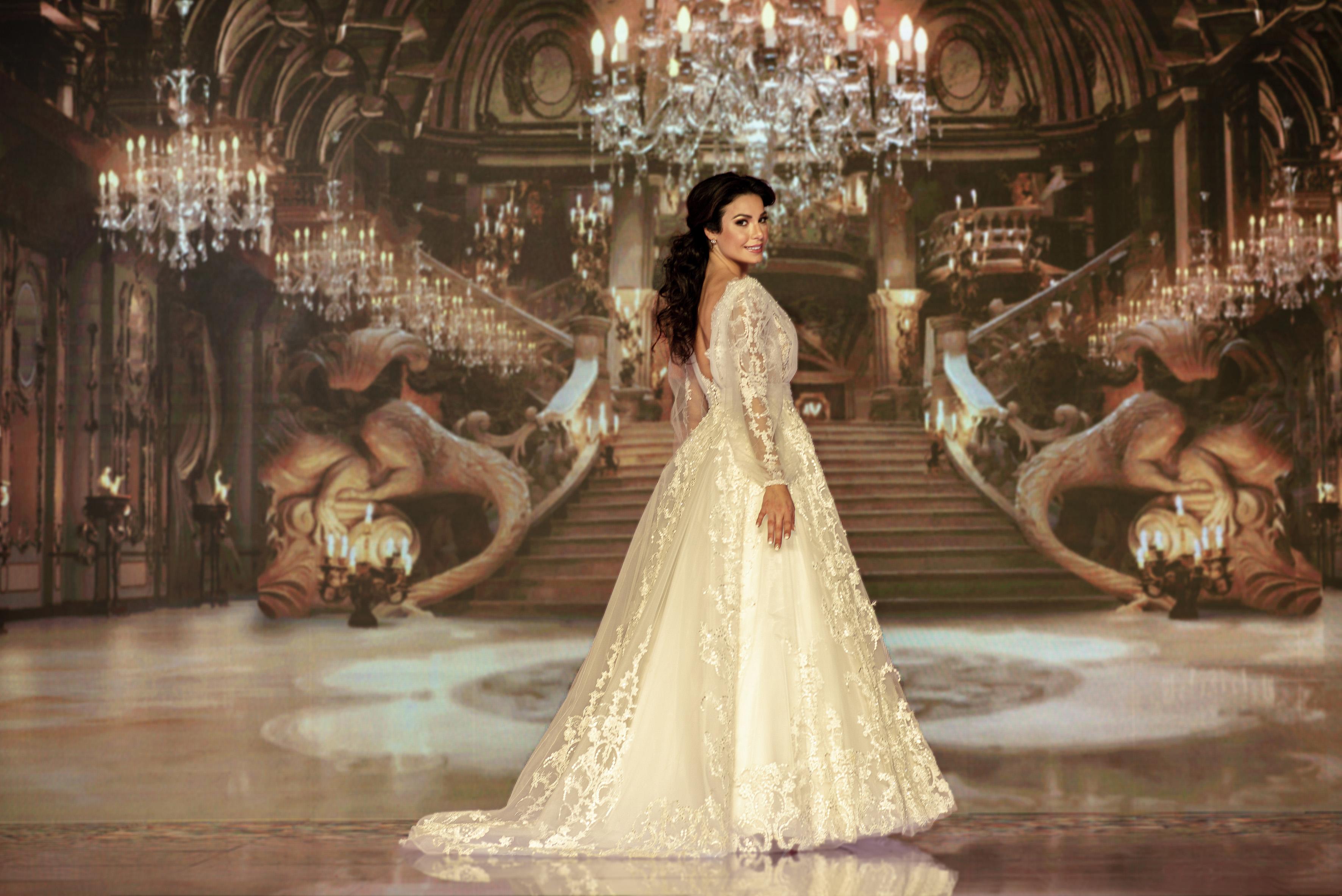 Julia Gama com vestido inspirado na Bela. Ela está com o corpo de lado, olhando para a câmera e sorrindo.