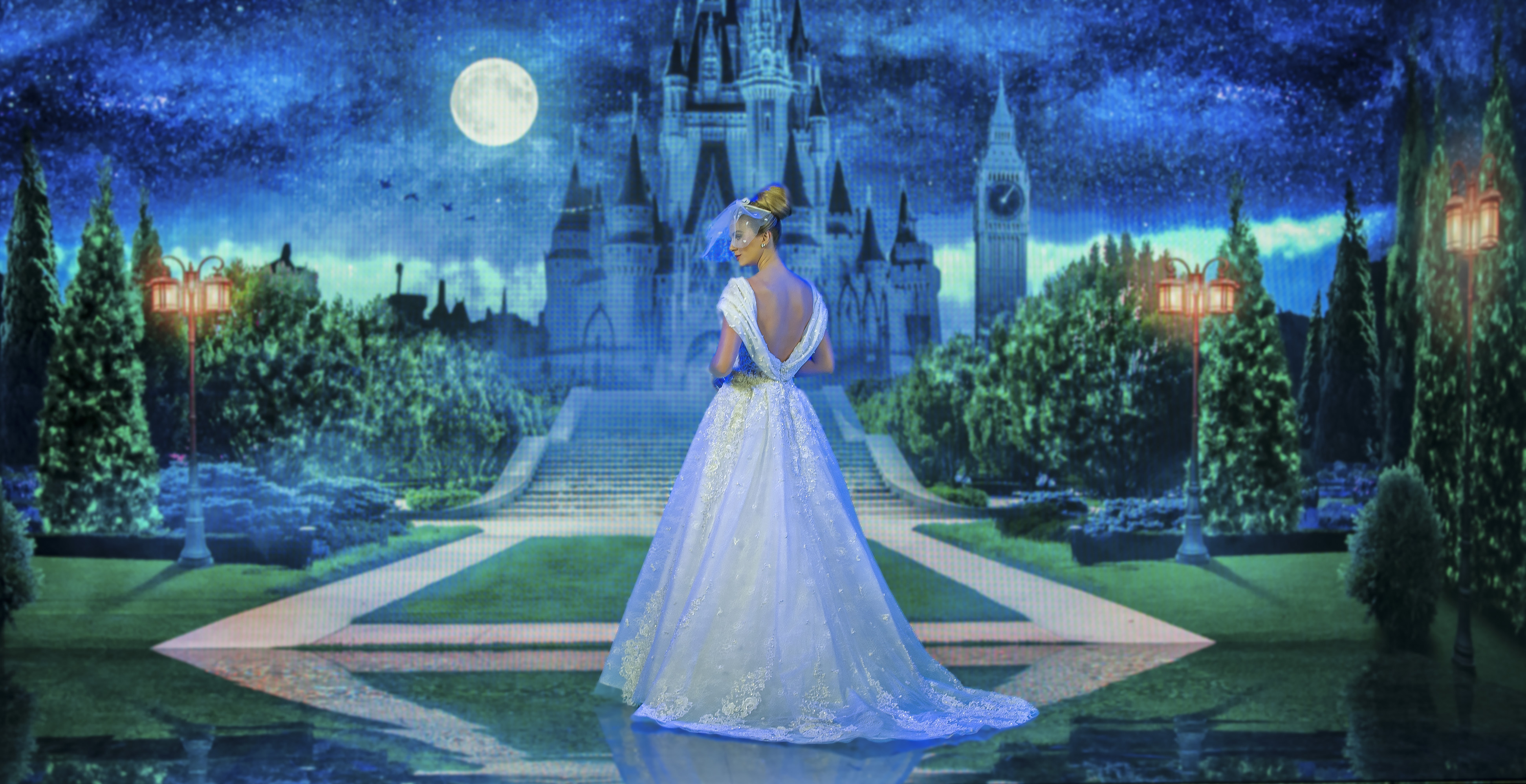 Marthina Brandt com vestido inspirado na Cinderela. Ela está de costas para um fundo que imita o castelo da Disney.