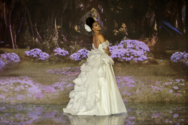 Raissa Santana com vestido inspirado na Tiana. Ela está de costas, olhando para o lado com expressão facial séria e cabeça inclinada para trás.