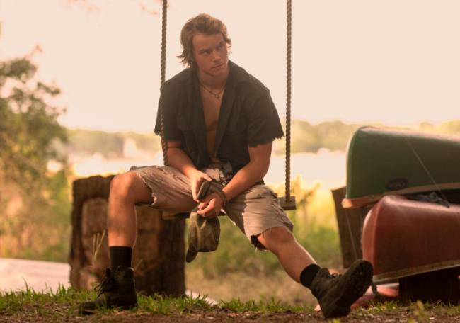 JJ sentado com camisa e short, ele usa coturno e está com uma expressão séria.
