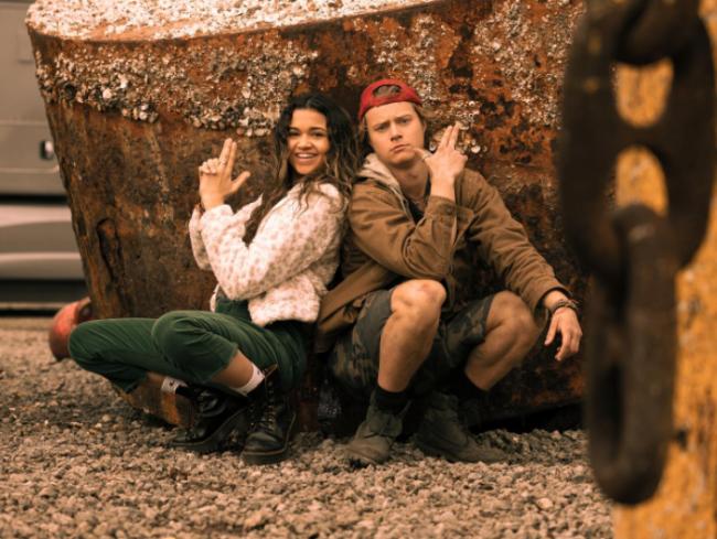 Kiara e JJ juntos sentados encostados em uma pedra com expressões sorridentes.