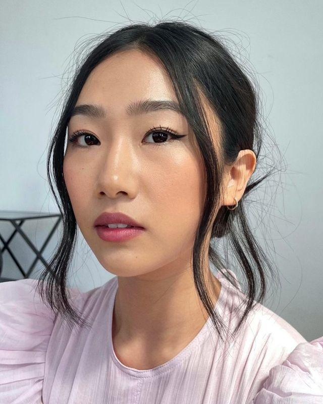 Selfie de uma mulher. Ela usa uma blusa rosa de manga bufante, cabelo preso em um coque baixo, brinco de argola dourado pequeno e maquiagem natural com mini delineado gatinho. Ela olha para a câmera e não sorri.