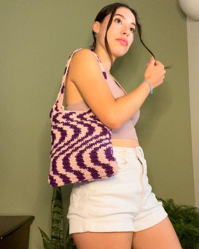 Foto de uma mulher em uma sala. Ela usa um top cropped lilás, short jeans branco, ecobag lilás e roxa de crochê e cabelo preso em um coque. Ela segura um fio da franja com a mão direita, olha para frente e não sorri.