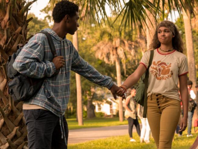 Dois personagens do seriado Outer Banks de mãos dadas em um espaço verde. O rapaz usa blusa azul e calça jeans e a menina camiseta branca com calça bege.