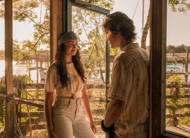 Kiara conversando com John B. Ela esta de frente e sorridente e ele de costas. Ela usa faixa na cabeça e camiseta.