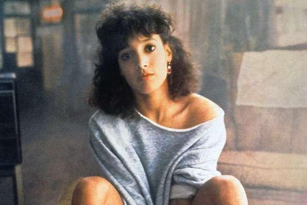 Personagem do filme Flashdance sentada com expressão séria