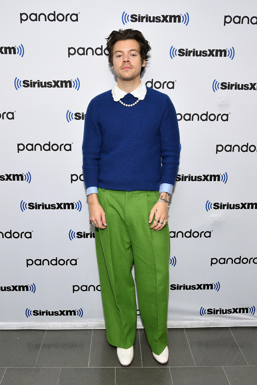 Harry Styles usando look com suéter azul e camisa branca com a gola aparecendo, calça pantalona verde e bota branca, além de colar de pérolas. Ele está olhando para a câmera com expressão facial séria.