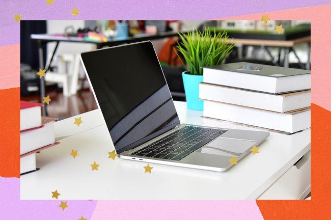 En la imagen aparece una computadora debajo de un escritorio junto a unos libros y una planta.