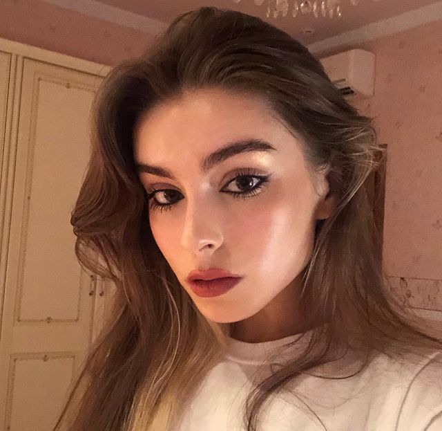 Selfie de uma mulher. Ela usa uma blusa branca, cabelo solto, maquiagem com pele natural, batom rosa queimado e olho com lápis de olho preto na linha d'água. Ela olha para a câmera e não sorri.