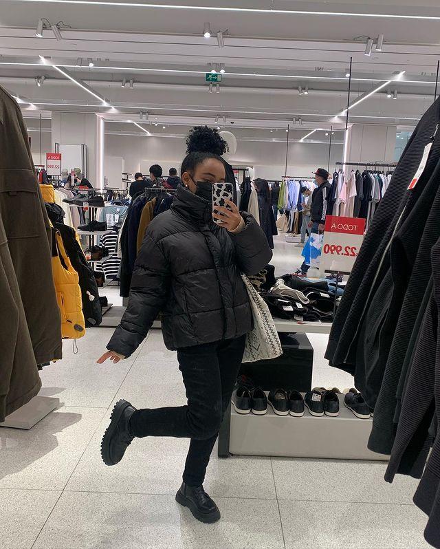 Selfie no espelho de uma mulher em uma loja de departamentos de roupa. Ela usa uma jaqueta puffer preta, calça skinny preta, bota preta, máscara preta, uma ecobag e cabelo preso em um coque alto. Ela está com a perna direita levemente levantada e olha para o celular que está com uma capinha com estampa de vaquinha.