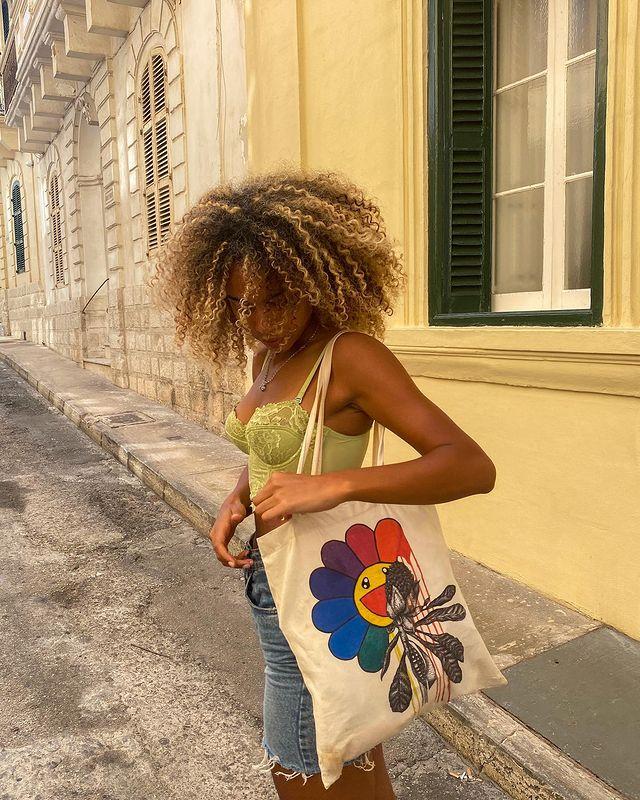 Foto de uma mulher na rua. Ela está com o cabelo crespo solto, usa um top rendado verde, shorts jeans e ecobag estampada com flor colorida. Ela olha para o chão e está virada levemente de lado para a foto.