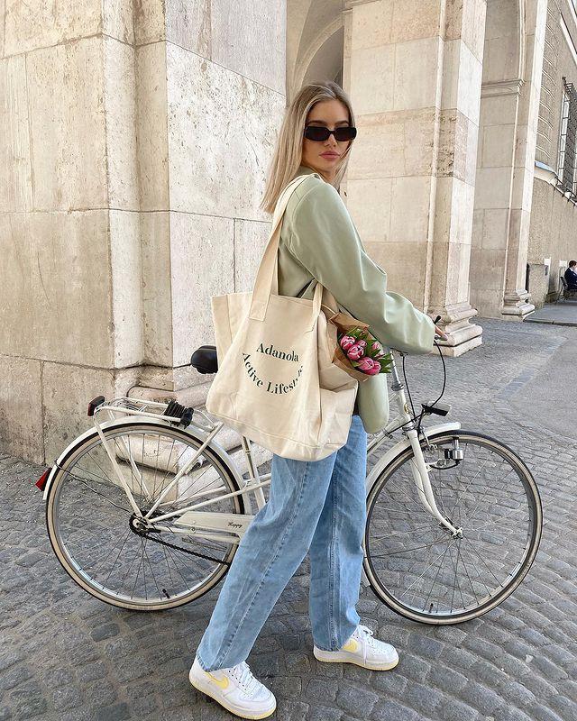 Foto de uma mulher em uma calçada. Ela usa uma blusa de moletom verde clara, calça mom jeans, tênis branco, bolsa ecobag e óculos de sol. Ela está ao lado e segurando uma bicicleta, ela olha para a câmera e não sorri.