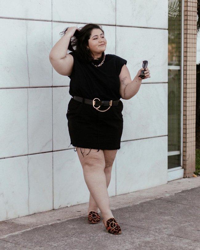Jovem posando com look preto em frente a parede. Uma de suas mãos está no cabelo.