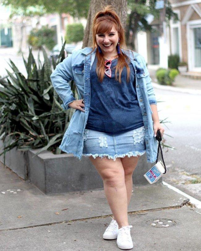 Jovem posando com uma das mãos na cintura usando blusinha e saia. Ela está sorridente.