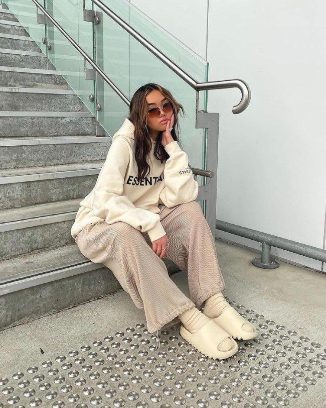 Jovem sentada em escada com expressão séria usando roupas na cor bege.