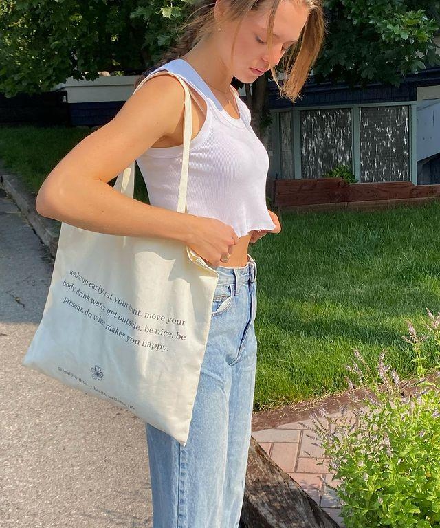 Foto de uma menina na calçada. Ela usa um top cropped branco, calça mom jeans e ecobag com estampa escrita preta e cabelo preso. Ela olha para o chão e está com as duas mãos segurando o top cropped.