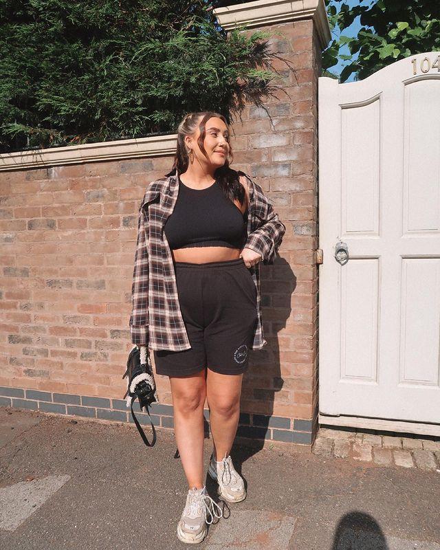 Foto de uma mulher em uma calçada. Ela usa uma regata preta, bermuda de moletom preta, camisa xadrez como sobreposição e segura uma bolsa preta com a mão direita. Ela olha para o lado e sorri levemente para a foto.
